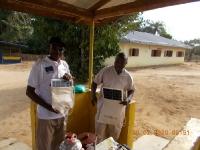 robert-und-campbell-vom-med-team-stehen-vor-ihrer-clinic-und-sind-gluecklich-ueber-die-gespendeten-solarpanels